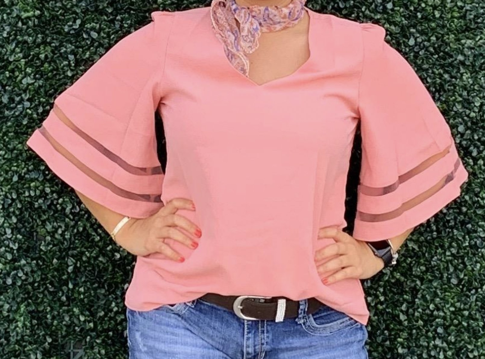 model wearing a flowing v-neck blouse with bell sleeves and mesh stripes in the sleeves