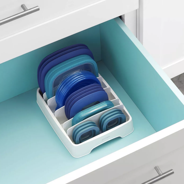 Lid storage organizer in drawer with various lids placed inside