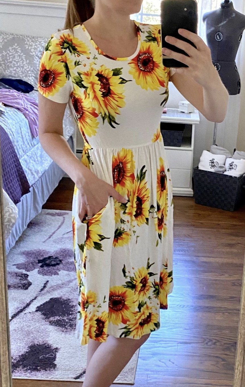 a person wearing a sun dress that stops at the knee and has pockets.
