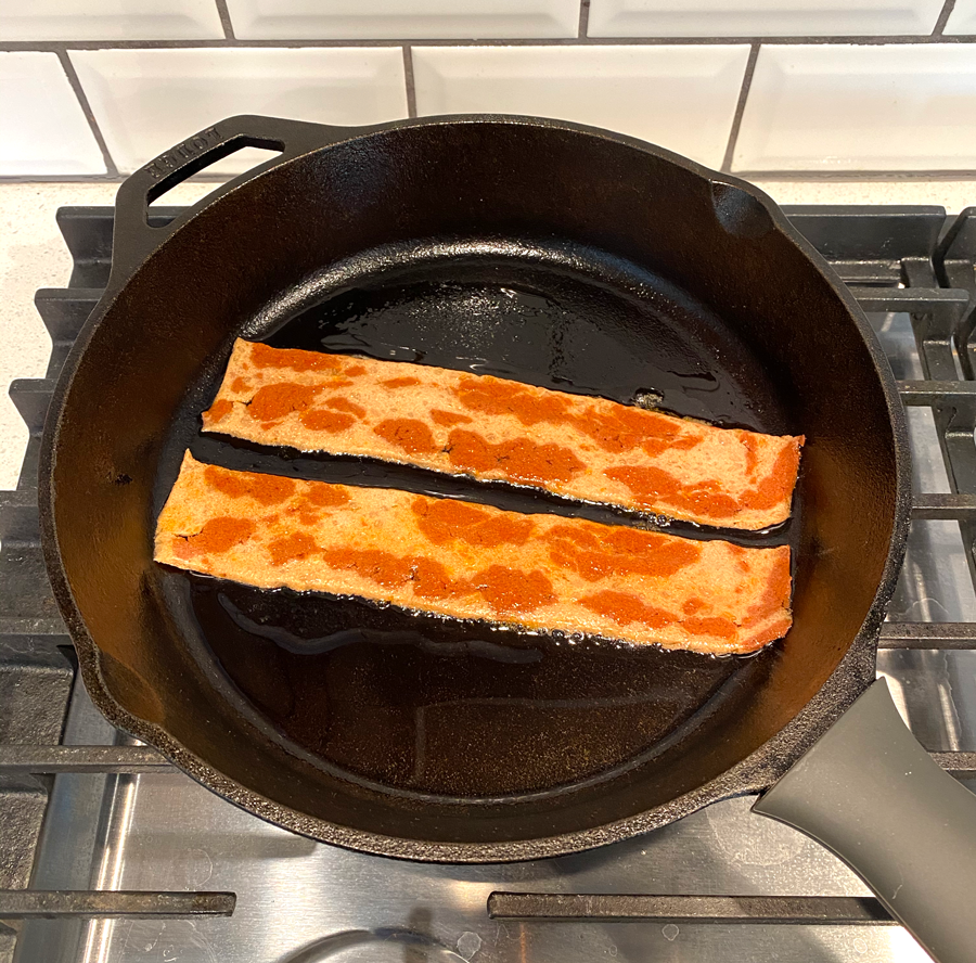 A skillet with two strips of the bacon in it