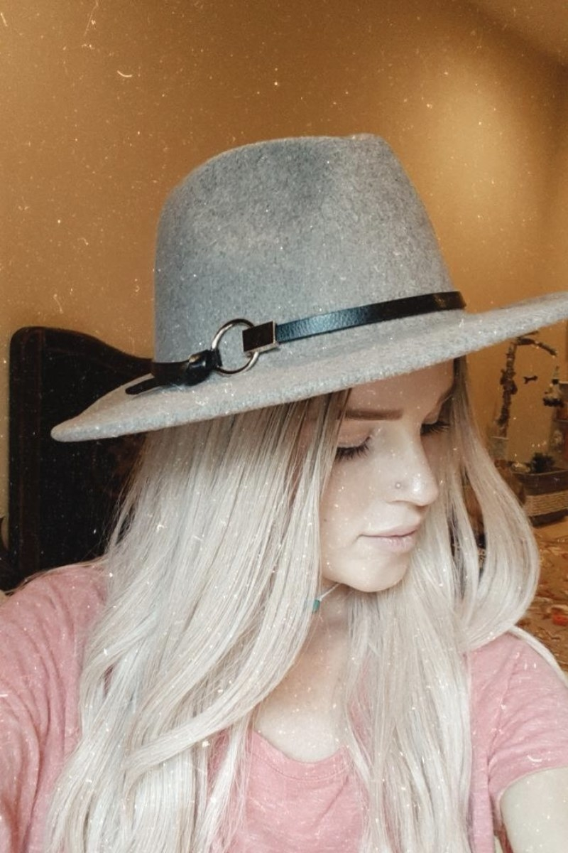 a model wearing a faux suede wide brim hat with a faux leather strap