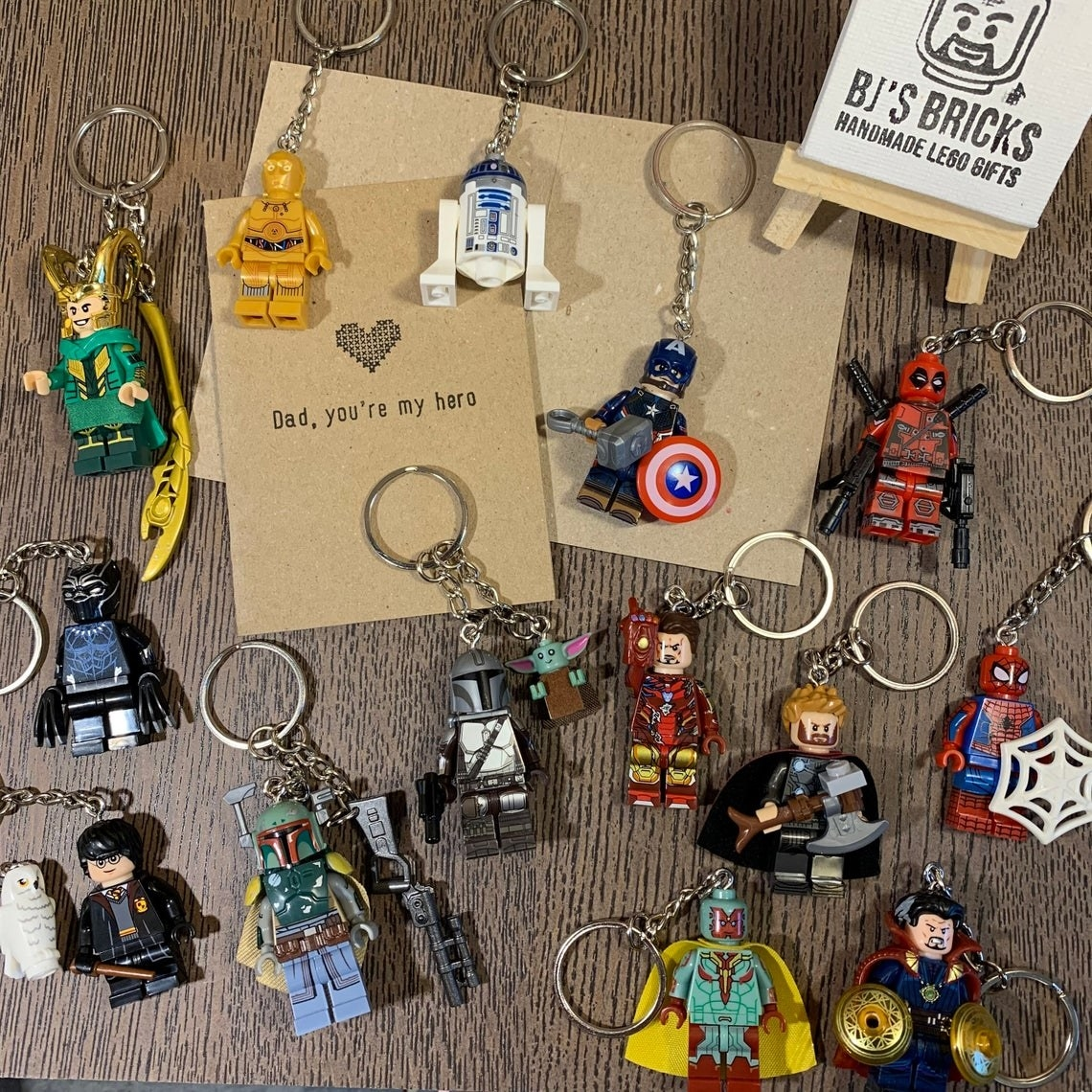 """the paper card that says """"dad, you're my hero"""" with a heart on it and a variety of different superhero keychains on a surface"""