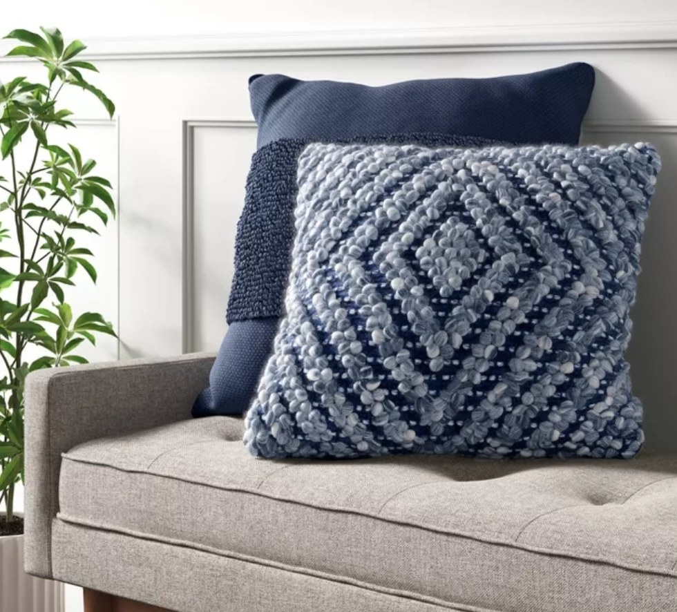 the pillow in two colors on a grey couch