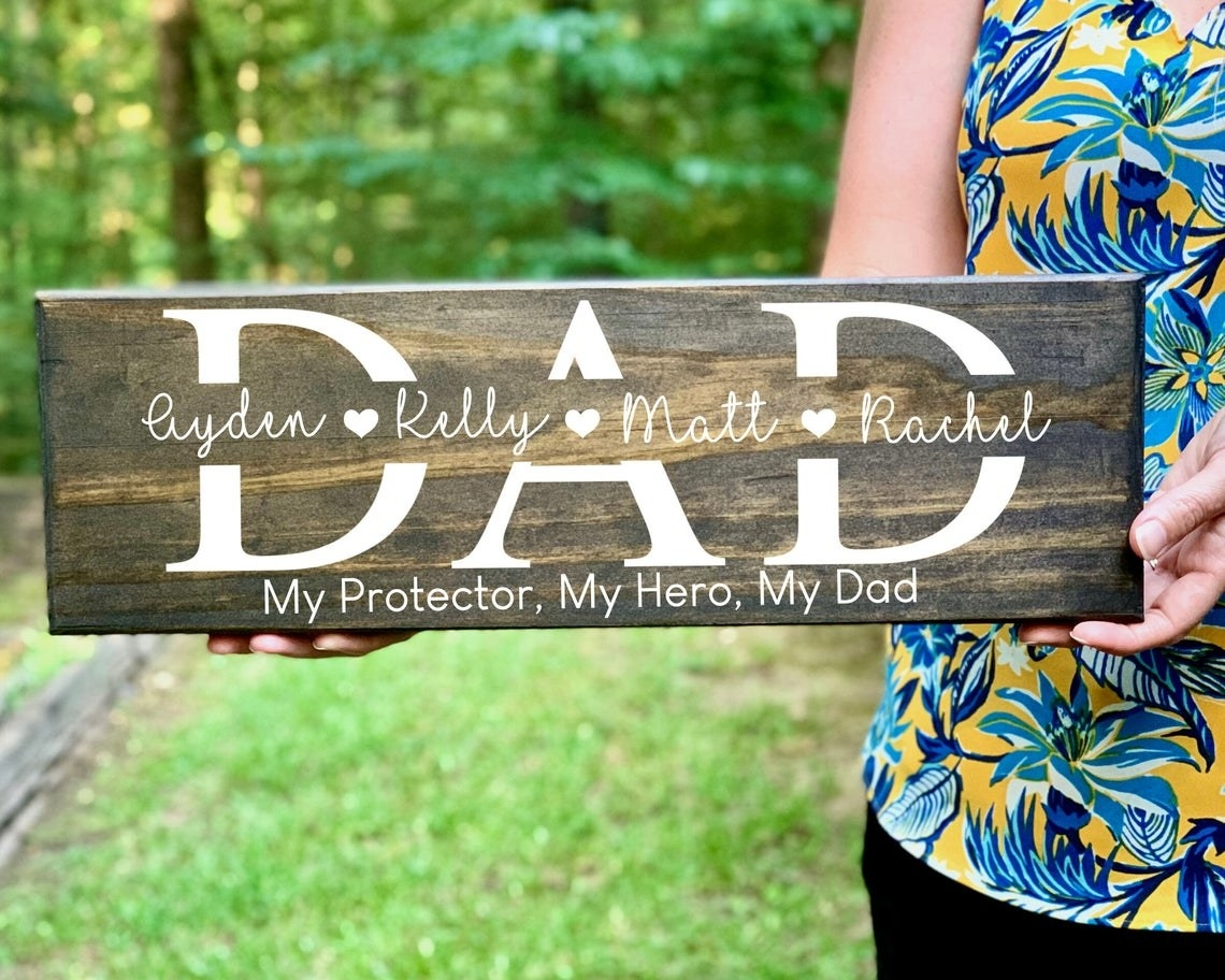 """person holding the wood sign that says dad, with four names through the middle and at the bottom it says """"my protector, my hero, my dad"""""""