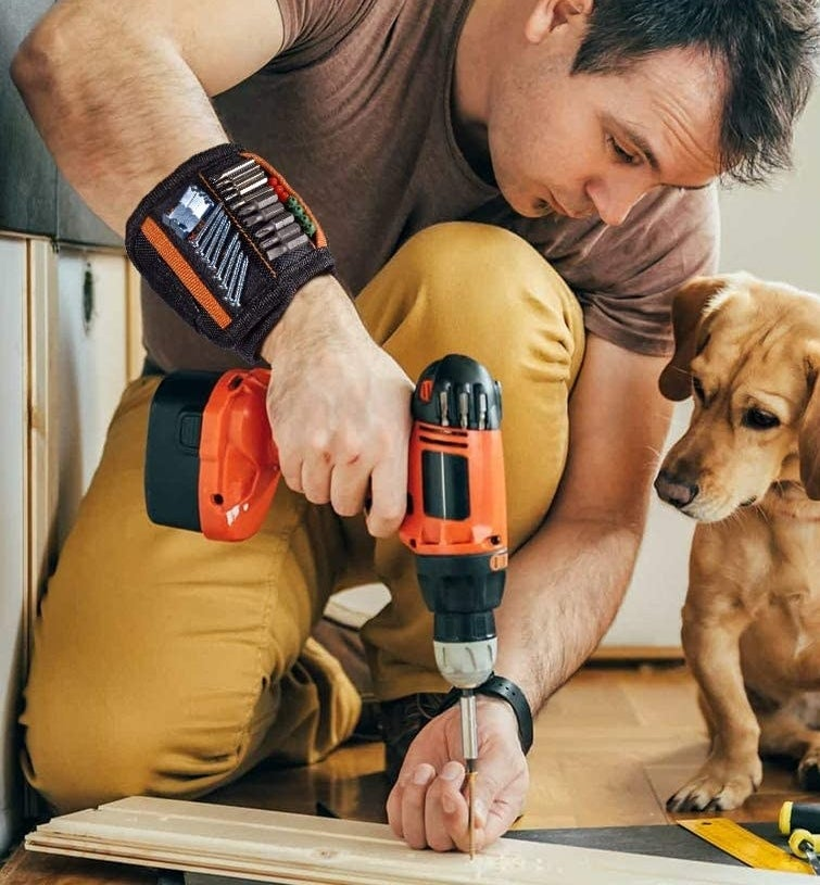model wearing the band with screws and bits sticking to it as he holds a drill