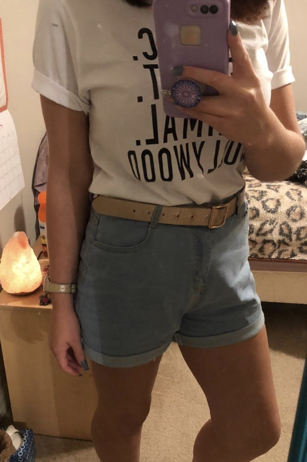 a person wearing a pair of high waisted jean shorts with a t-shirt tucked in