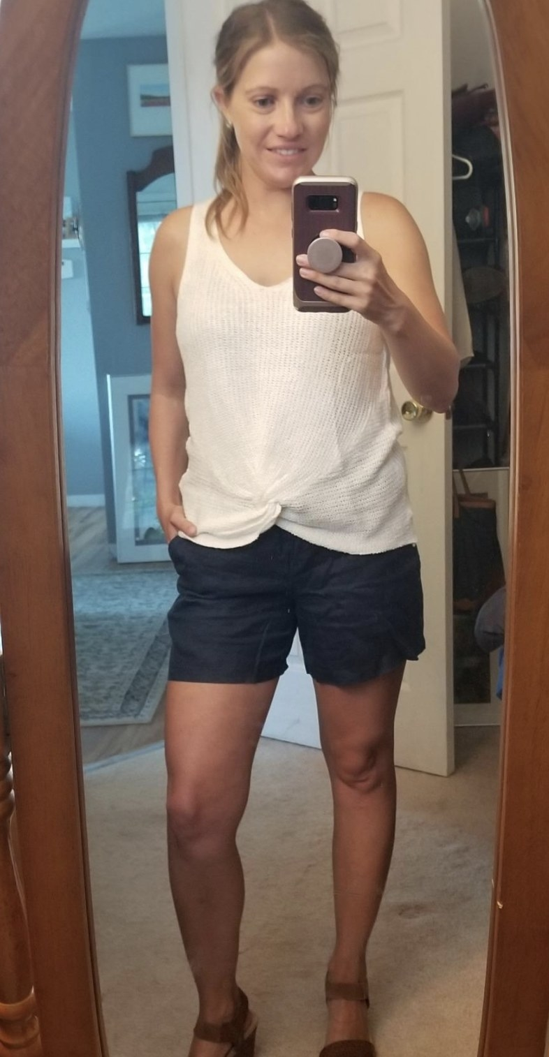 a person wearing navy linen shorts with a white tank top