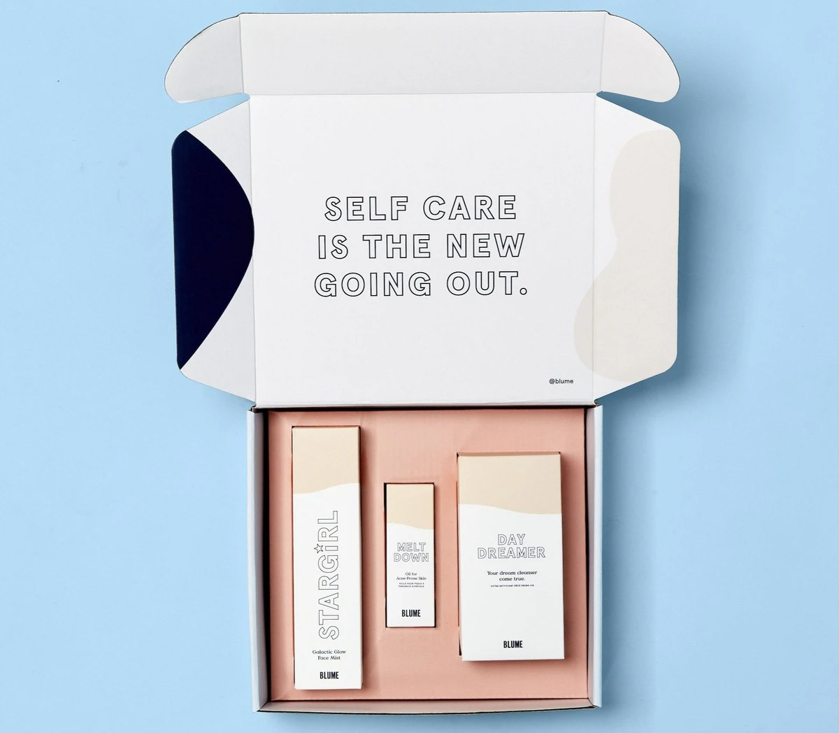 A gift box with a three beauty products in packaging inside