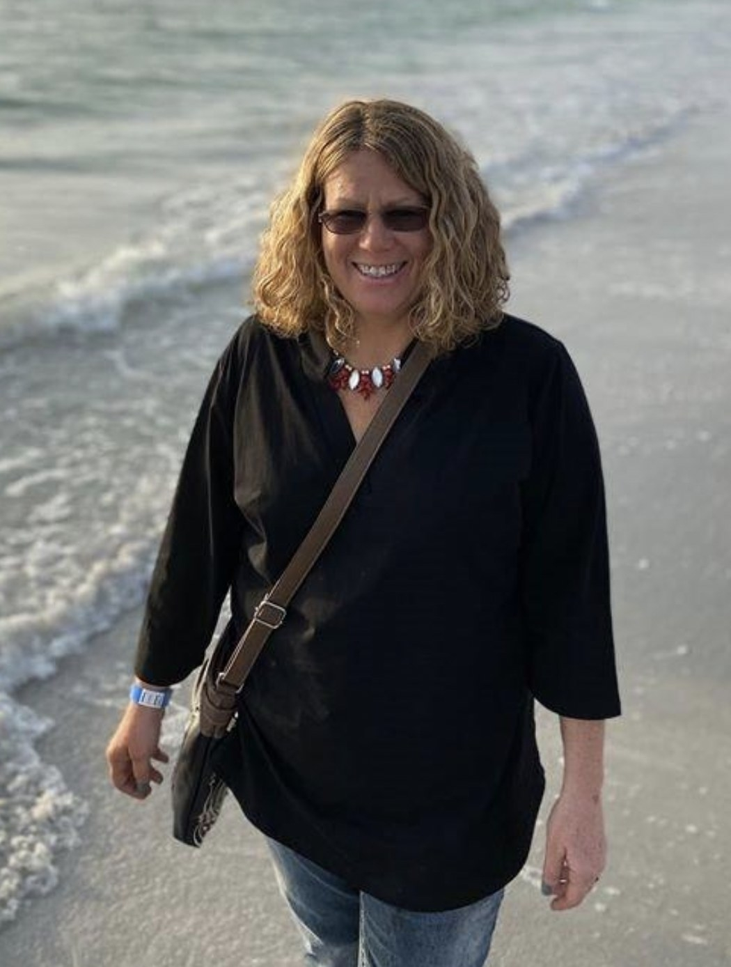 a person walking on a beach wearing a black tunic shirt