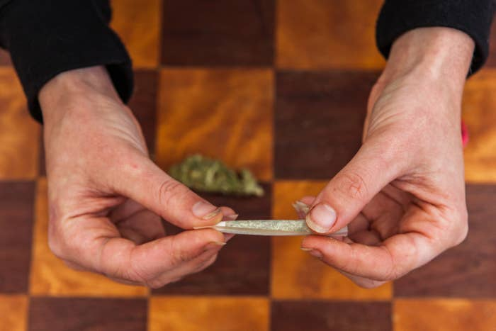 Close-up of two hands rolling a joint