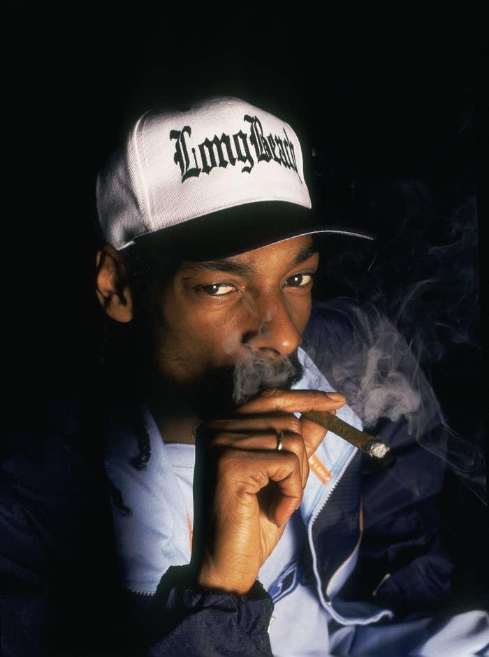 "Snoop Dogg smoking and wearing a ""Long Beach"" cap"