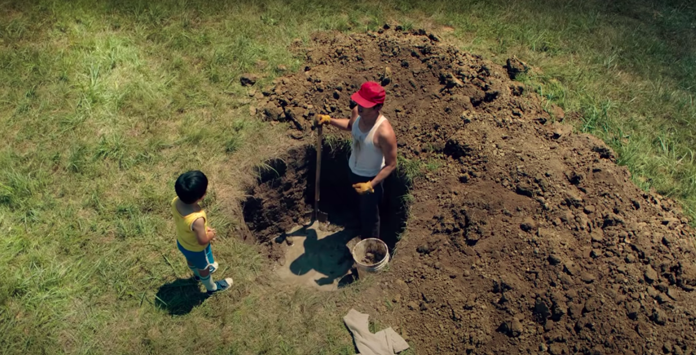 """Steven Yeun digging and well and talking to his son, Alan S Kim, in """"Minari"""""""