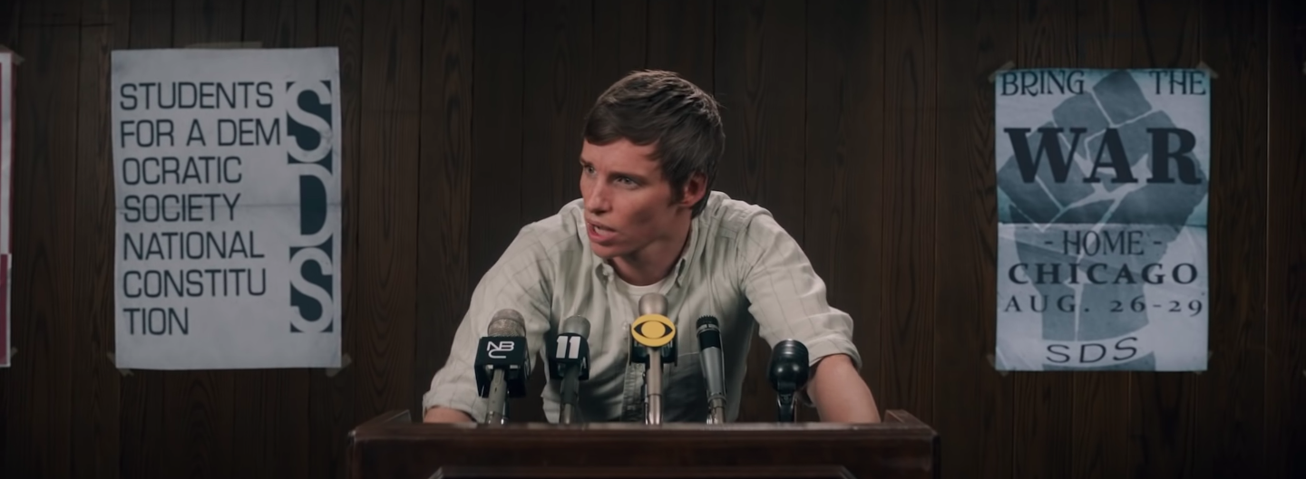 """Eddie Redmayne talking at a podium in """"The Trial of the Chicago 7"""""""
