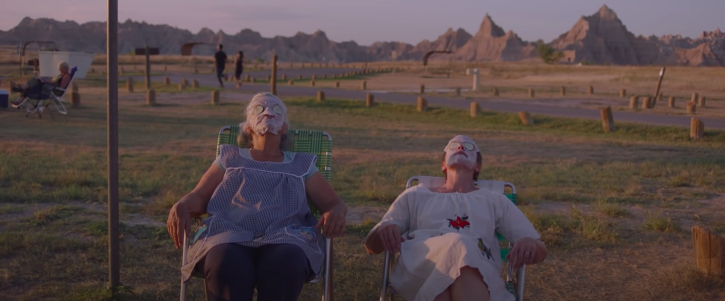 """Linda May and Frances McDormand wearing face masks and sitting in lawn chairs in """"Nomadland"""""""