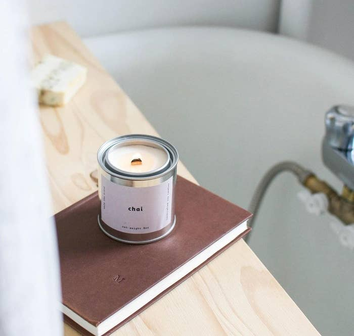 A lit candle in a metal tin resting on a book near a bathtub
