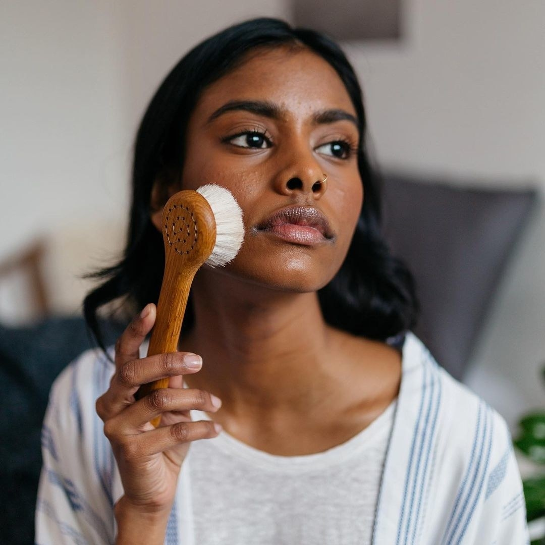 A person using a soft small facial brush on their skin