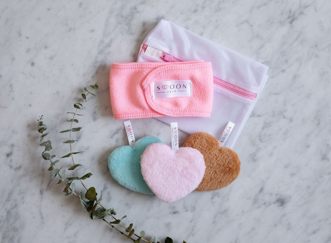 Three heart-shaped cleansing pads, a headband, and a laundry bag in a pile