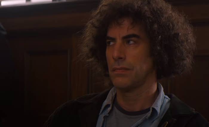 """Sacha Baron Cohen looking to his right in """"The Trial of the Chicago 7"""""""