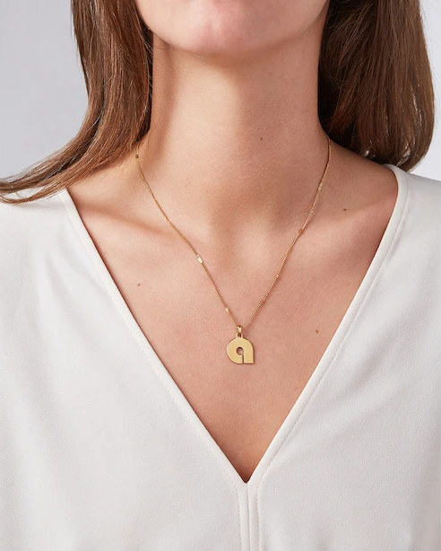 A person wearing a necklace with a pendant in the shape of the letter A