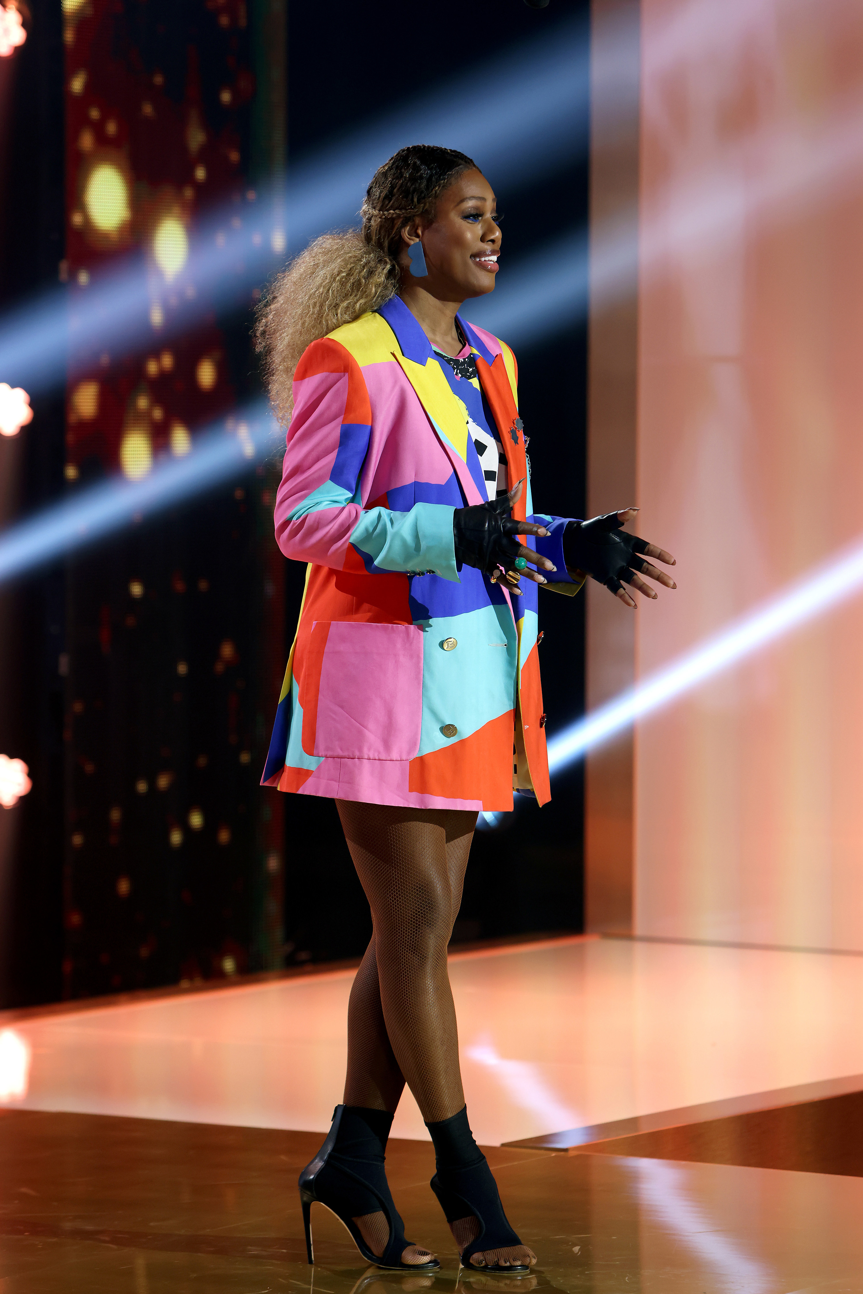 Laverne wears a red, blue, pink, and turquoise color block blazer dress