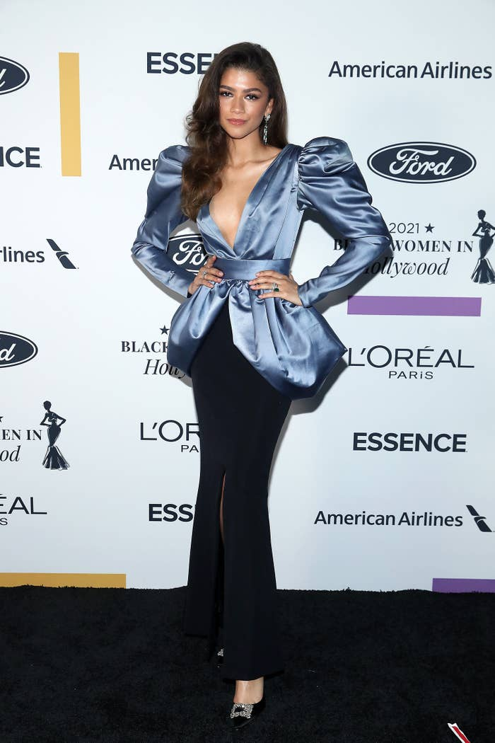 Zendaya wears a black pencil skirt with a center slit and a blue puffed sleeve silk top with a v neck