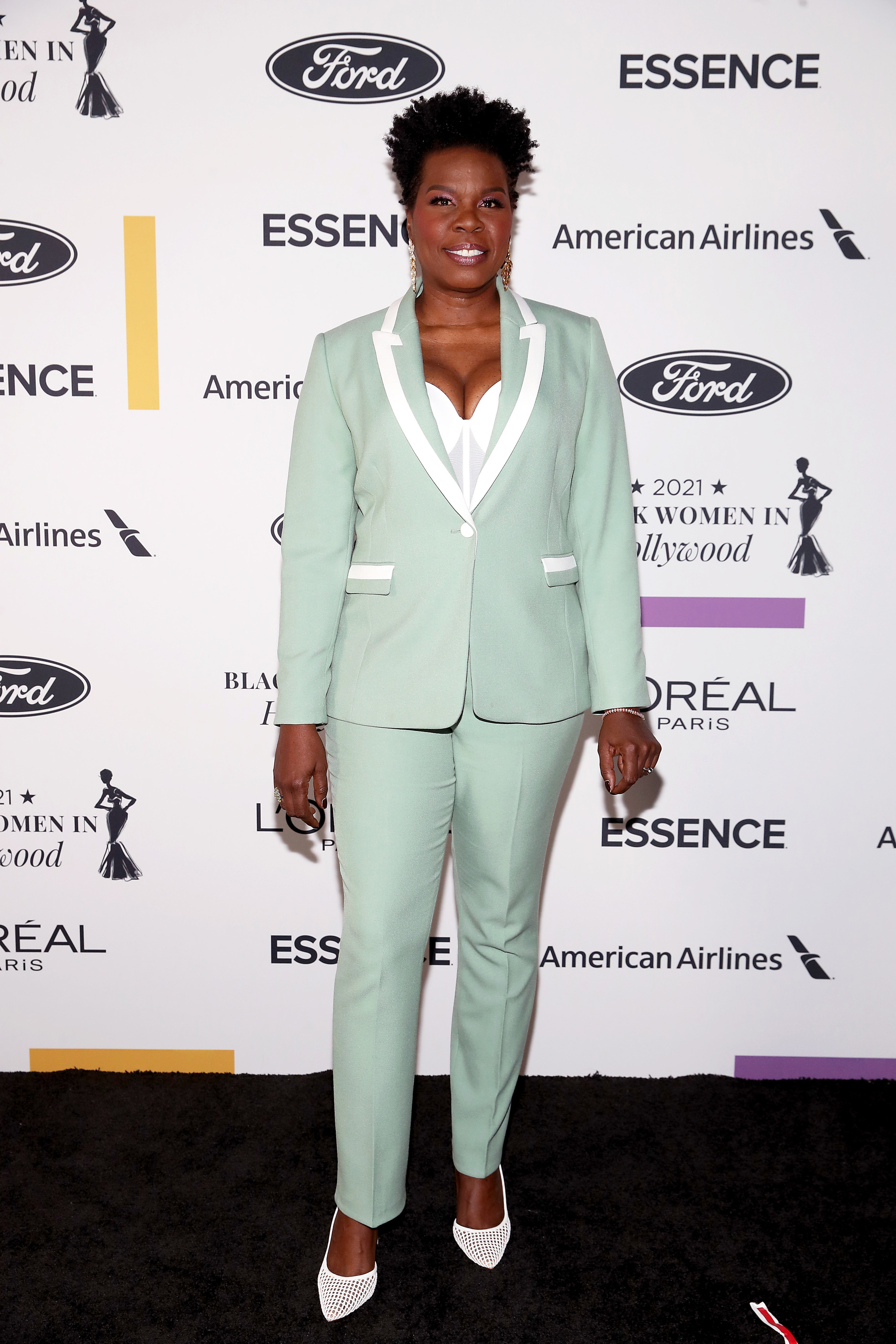 Leslie wears a Tiffany blue suit with white piping details