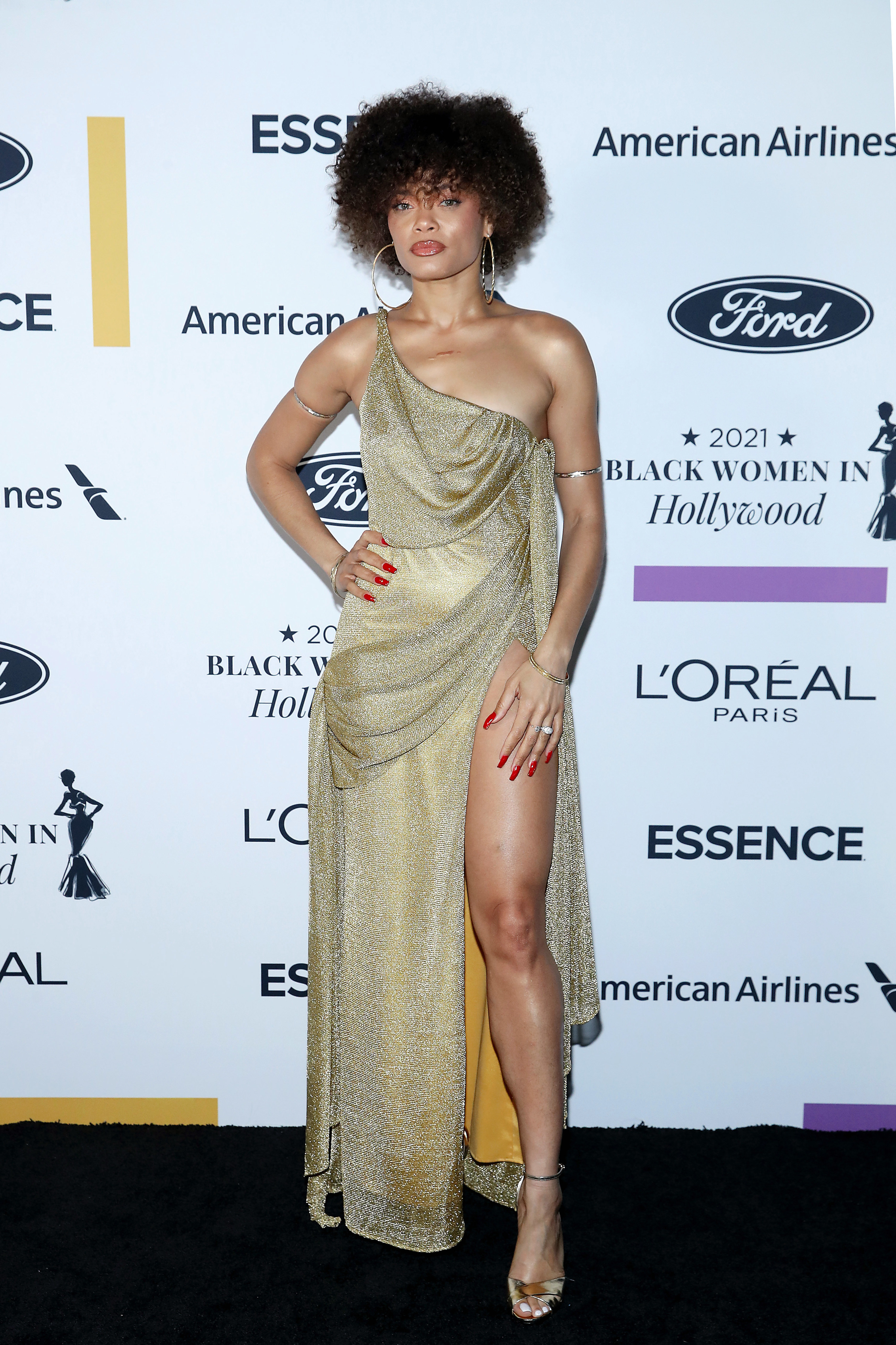 Andra wears a shimmering gold gown with one shoulder and a thigh high split