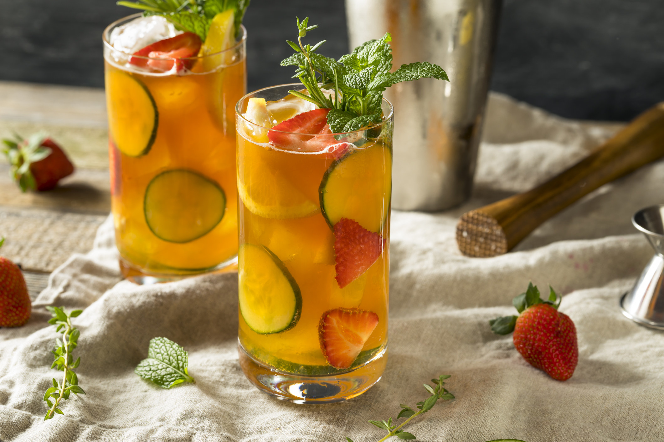 Two Pimm's Cups with lime and strawberries.