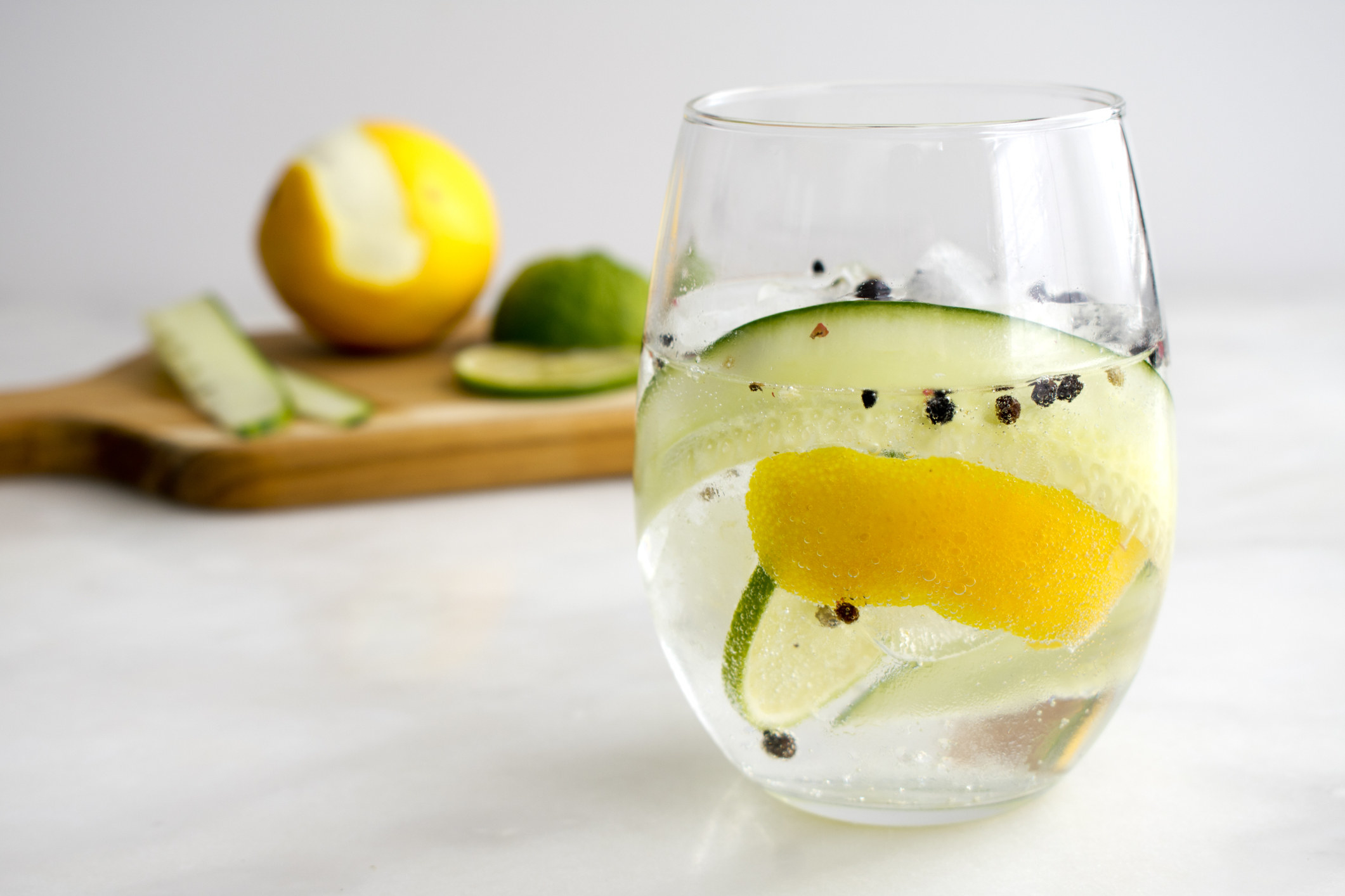 Gin and Tonic with whole black pepper, lemon rind, and cucumber.