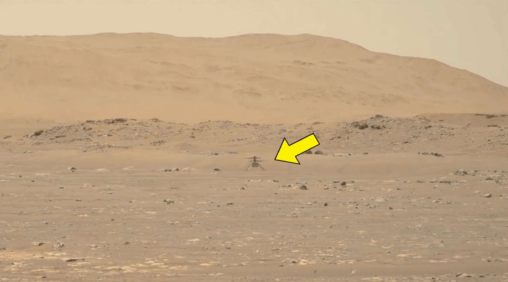 Ingenuity hovering above the surface on Mars