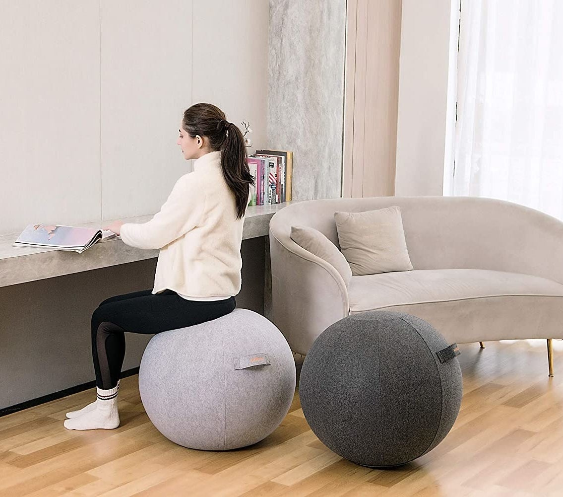 A person sitting on a ball next to a second ball in a living room