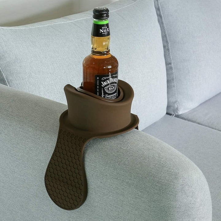The brown plastic cup holder attached to the arms of a couch with a beer bottle in it