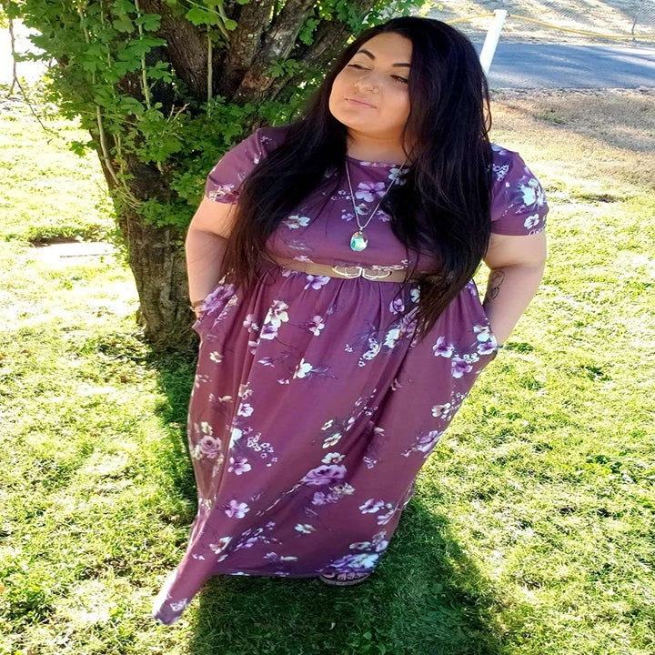 reviewer wearing the dress in a purple floral print with a belt around their waist