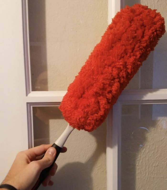 A person holding a red duster