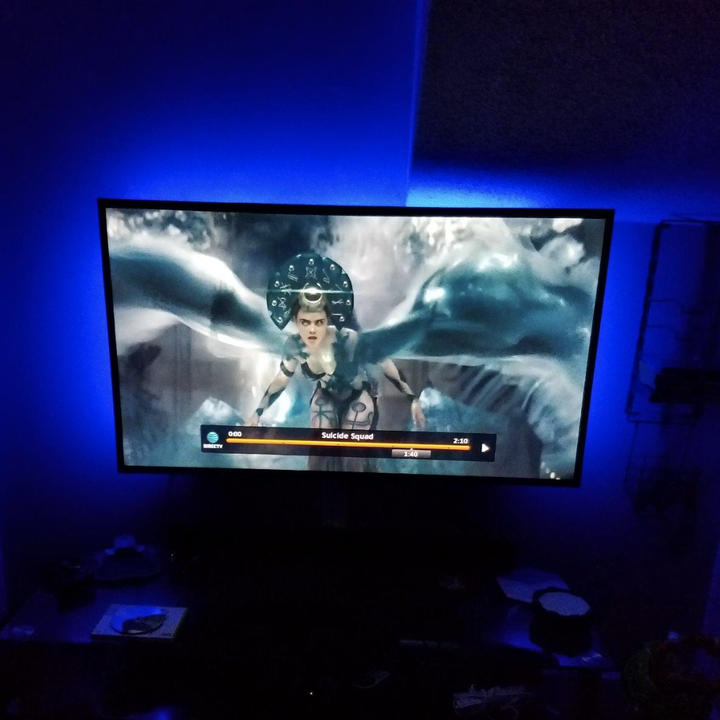 A television with a blue blacklight around the edges popping the image against the dark
