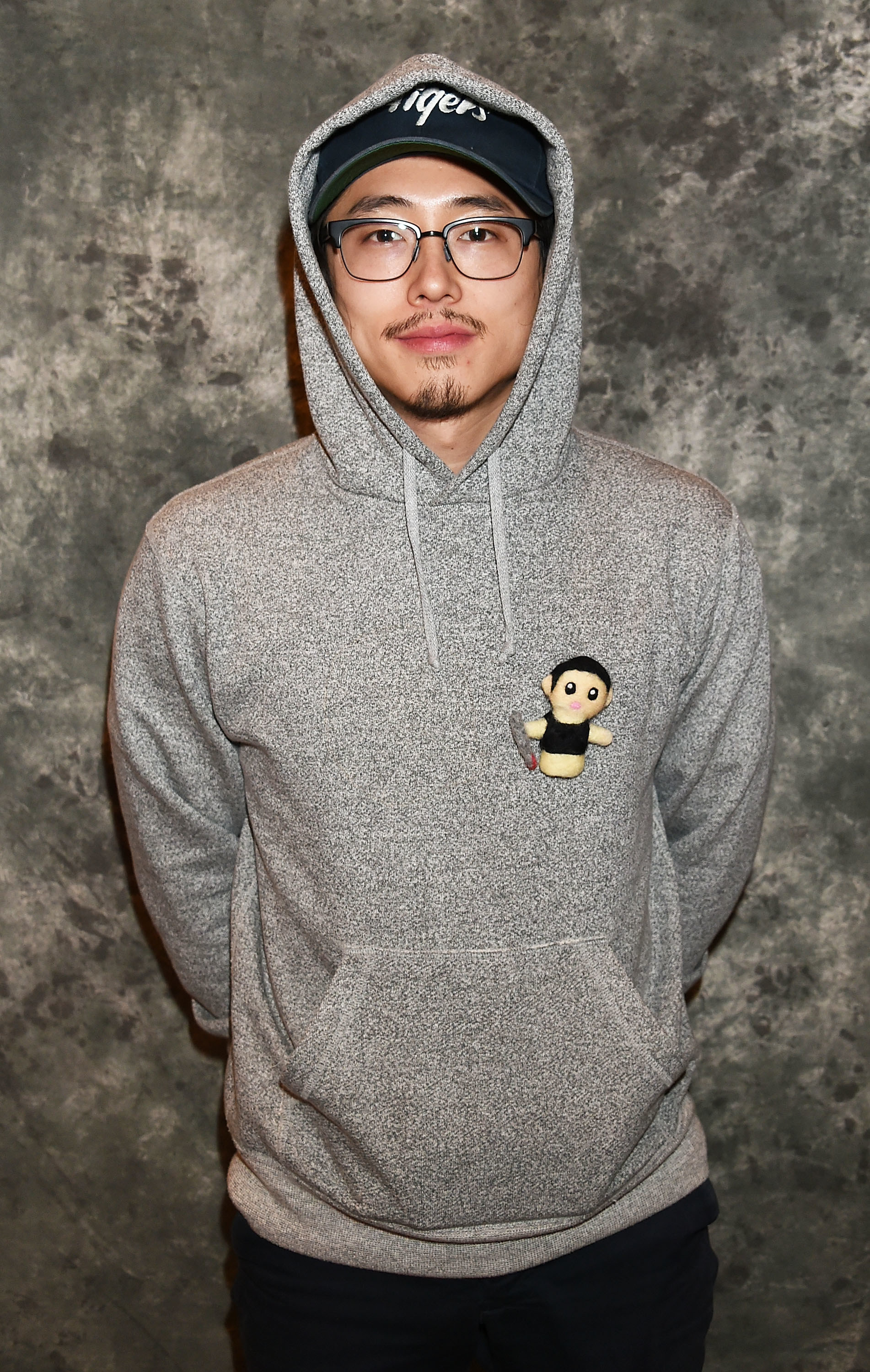 A bespectacled Steven  in a gray hoodie and baseball cap
