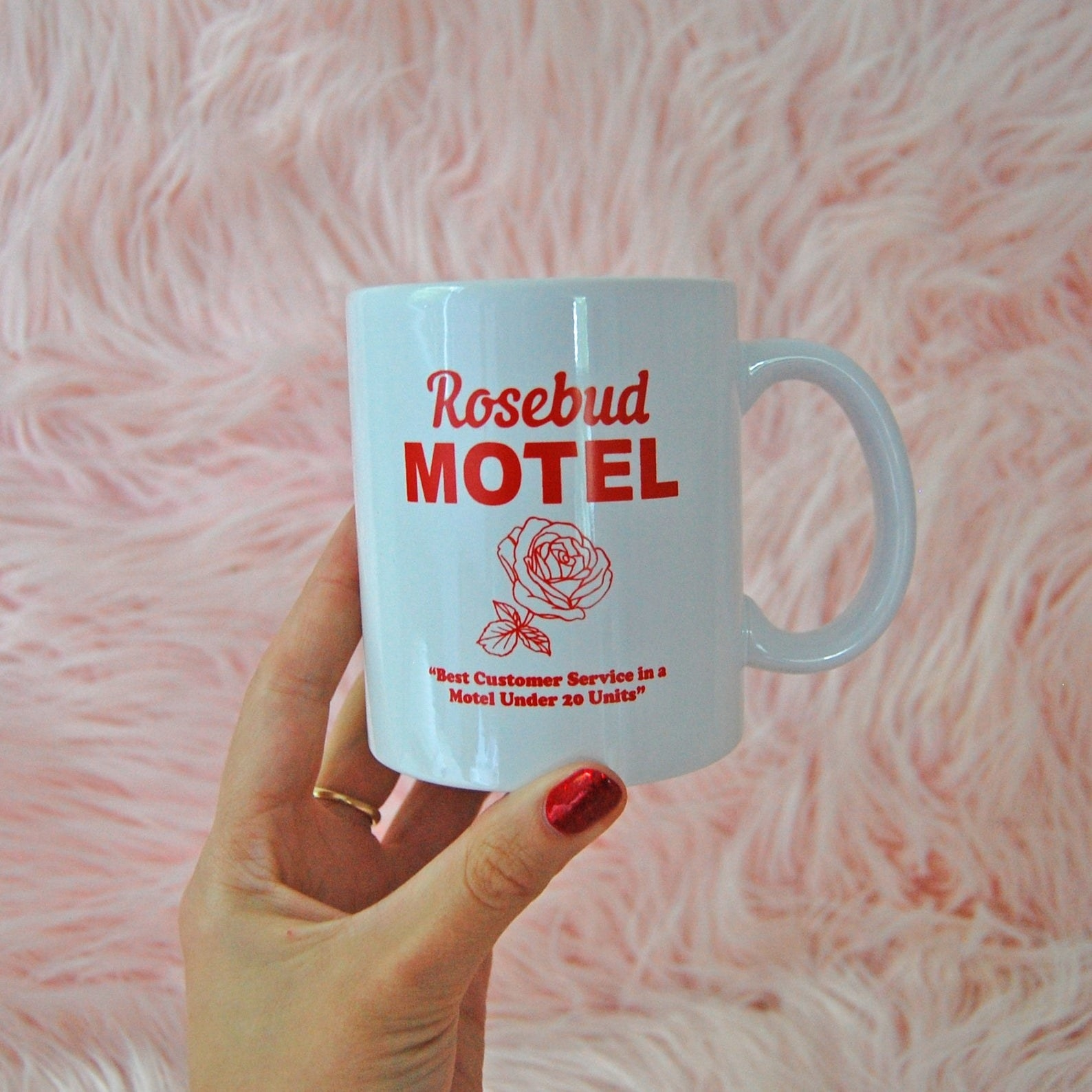 A white mug that says Rosebud Motel with a rose on it