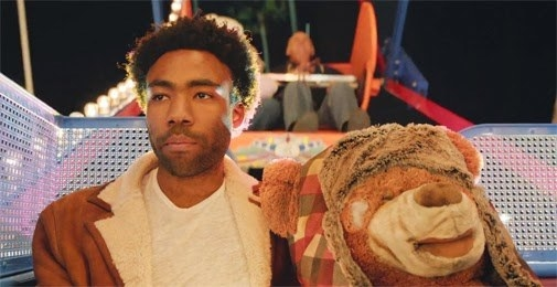 "Childish Gambino in his ""3005"" music video, on a ferris wheel with a teddy bear"