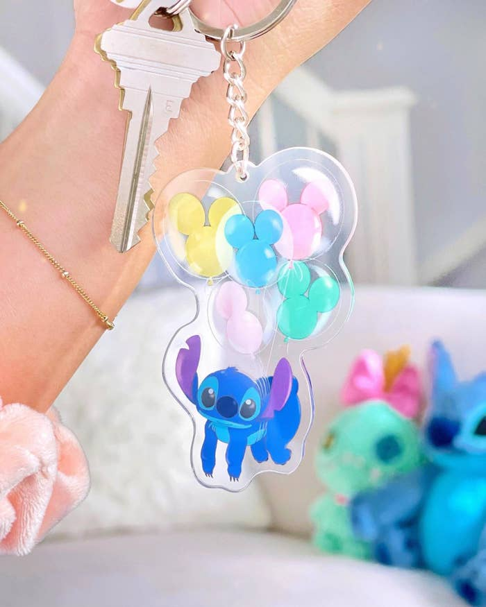 a keychain of stitch floating from mickey shaped balloons