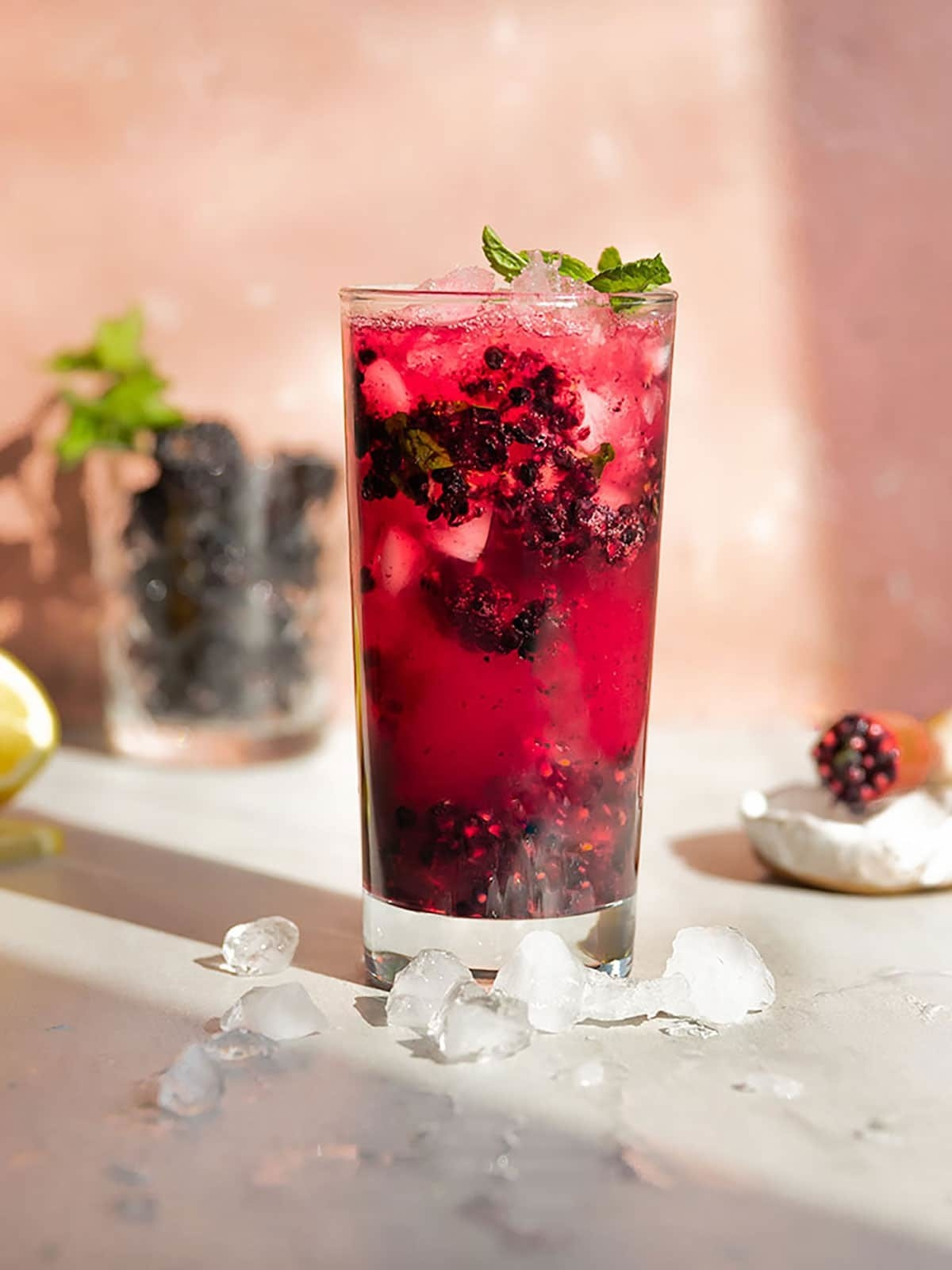 A glass of mojito with muddled blackberries.