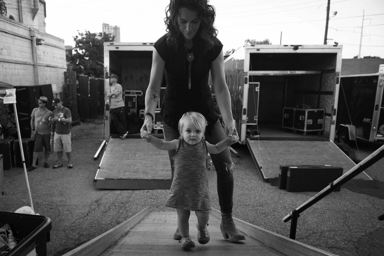 A mother walks behind her toddler child up a ramp