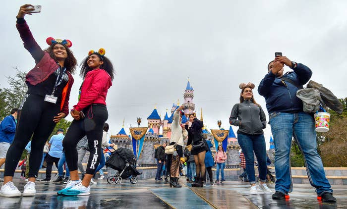 Guests taking selfies in front of the castle at Disneyland