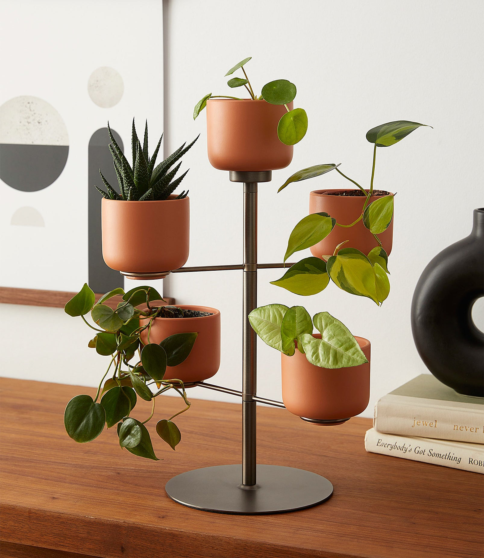 A plant stand with five rotating terracotter planters