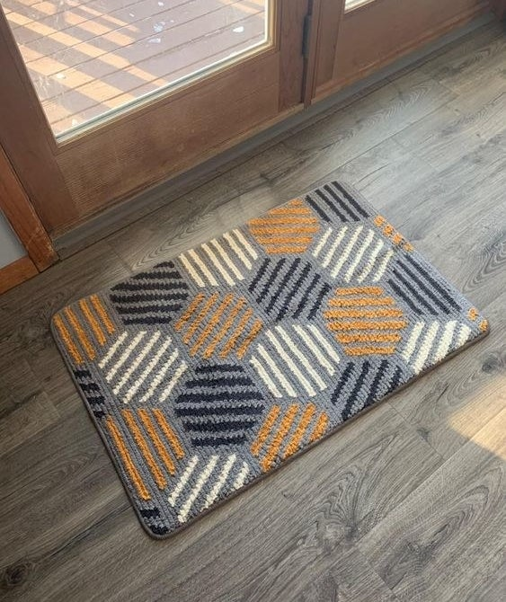 Reviewer's picture of the gray and orange doormat