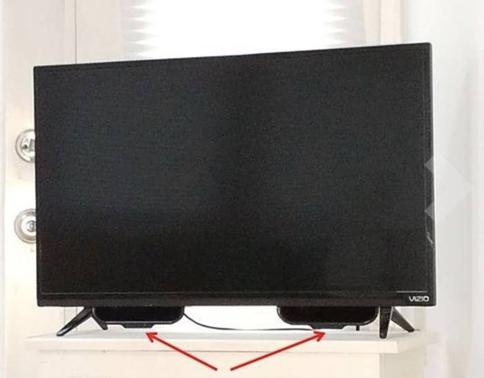 """A reviewer's television with two black """"scoops"""" installed on the bottom of the screen"""