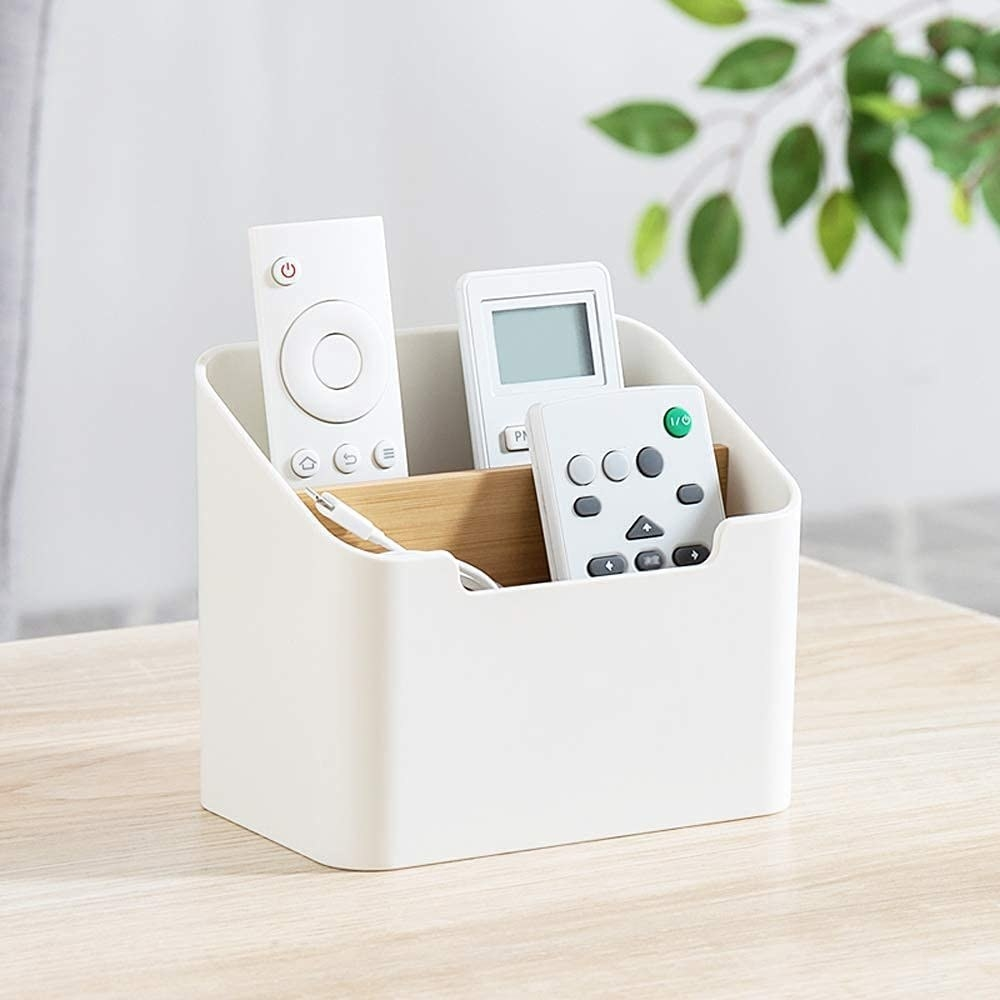 A white and light wood rectangle-shaped holder with two compartments for remotes to rest in upright