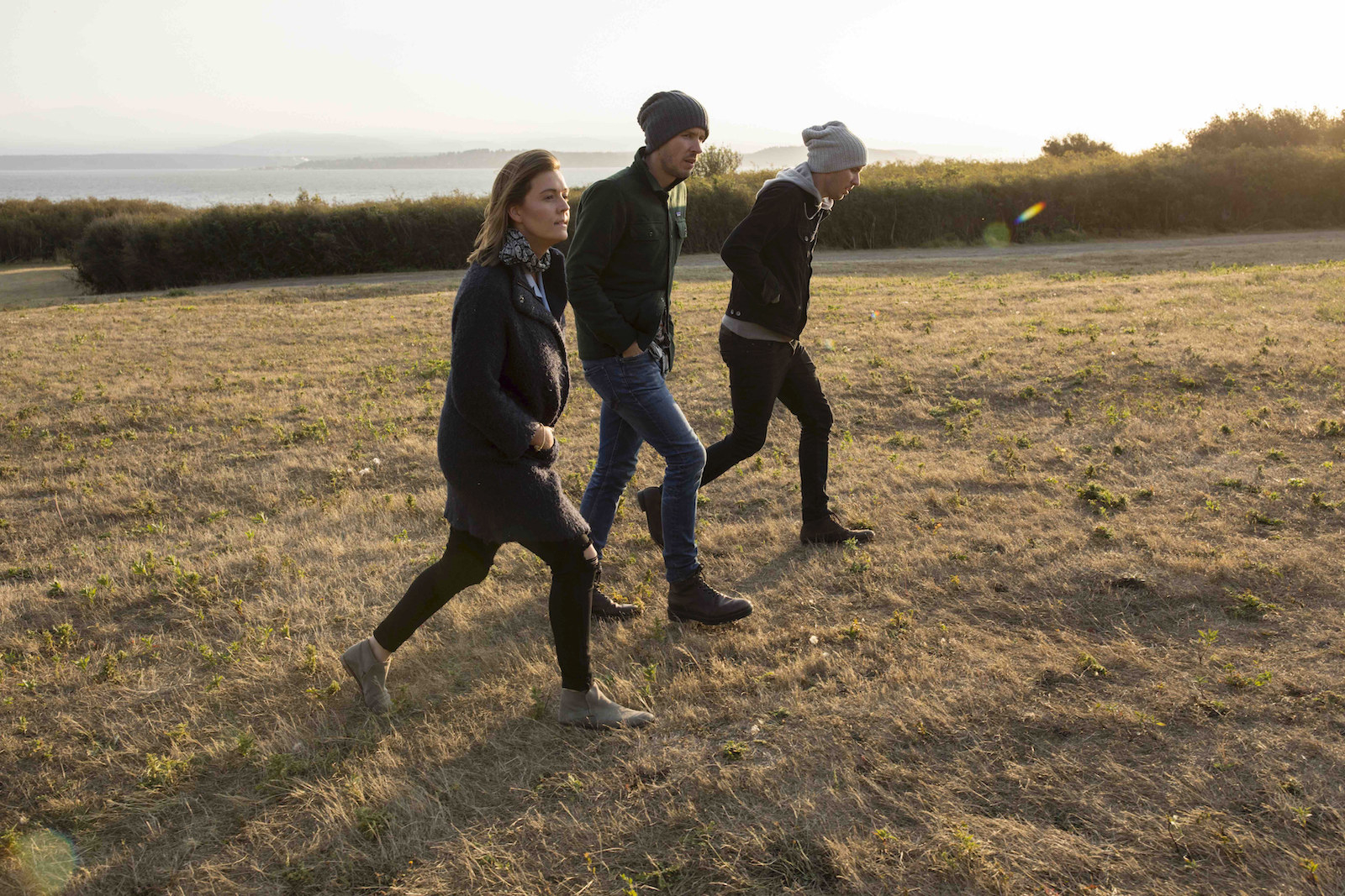 Brandi walks with two men in a field, all dressed in jeans and warm coats