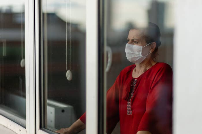 woman in a mask looking out a window