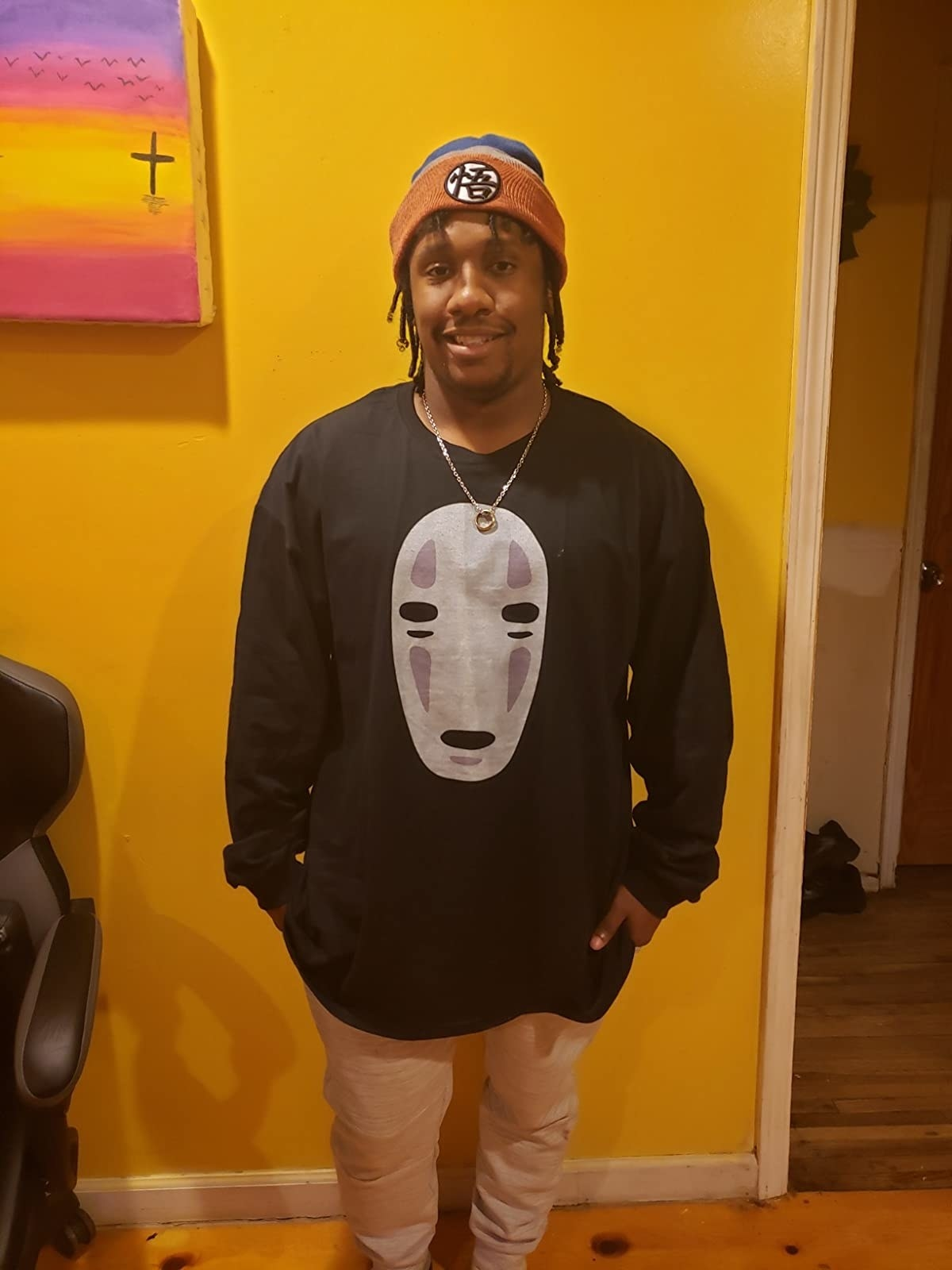 reviewer wearing the black long-sleeve tee with a large graphic of No Face's face