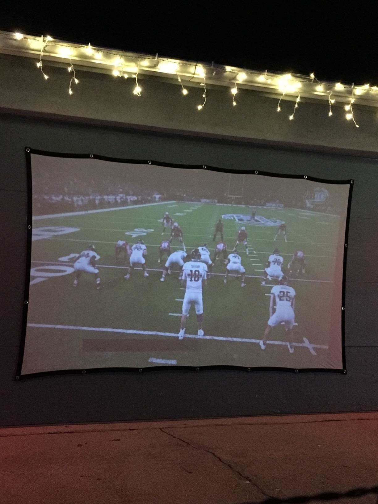 a screen with a football game projected onto it